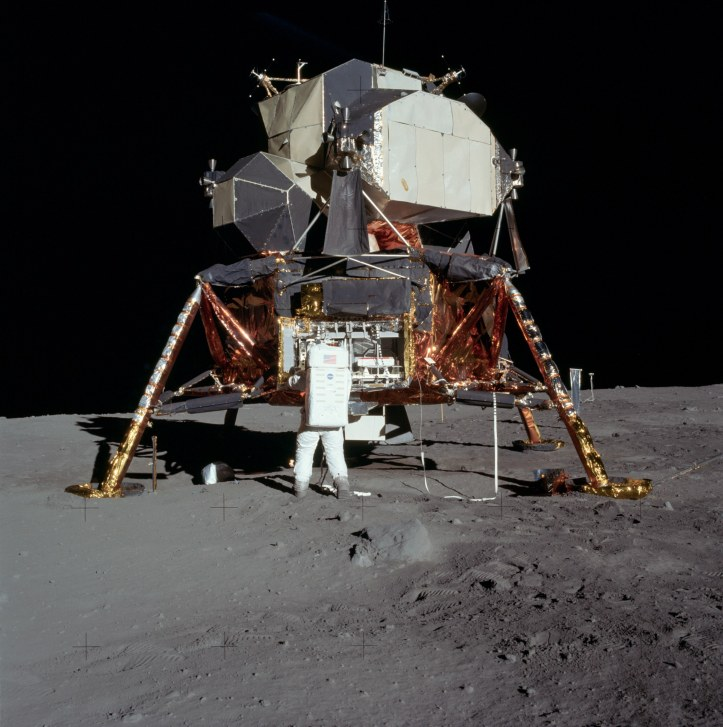 Buzz Aldrin descară echipamentul destinat experimentelor științifice (realizate ulterior și controlate de pe Terra). Modulul lunar se vede în toată splendoarea lui. Foto: NASA Apollo Lunar Surface Journal