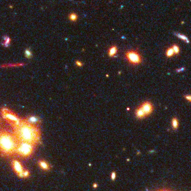 Mica pată roșie din centrul imaginii este obiectul în cauză. Foto: Undeva în această imagine se află una dintre cele mai îndepărtate galaxii din Univers. Foto: NASA, ESA, W. Zheng (JHU), M. Postman (STScI), and the CLASH Team