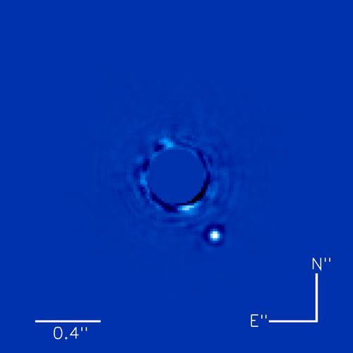 Beta Pictoris, prima stea cu planetă observată.  Vedem lumina în infraroșu emisă de o planetă puțin mai mare decât Jupiter (punctul alb). Steaua se află în centru și este ascunsă pentru a nu polua datele. Foto:  Christian Marois, NRC Canada