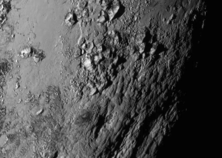 Imagine cu Pluto luată cu 1,5 ore înainte de apropierea minimă, de la 77.000 km depărtare. Vărfurile muntoase ating 3500 m înâlime și sunt foarte noi sau în proces de formare. Foto: NASA / JHUAPL / SwRI